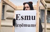 ФОТО: Возле здания Сейма защитники животных посадили девушку в клетку