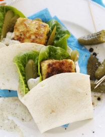 Tortiljā ietīta zivs fileja ar lapu salātiem un marinētiem gurķīšiem