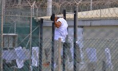 epa02134071 In this photo, reviewed by a U.S. Department of Defense official, a Guantanamo detainee does pull-ups inside an exercise area at the detention facility at Guantanamo Bay U.S. Naval Base, Cuba, 27 April 2010.  EPA/Michelle Shephard / POOL POOL
