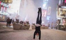 Dienas ceļojumu foto: Tūrists pozē, stāvot uz rokām, sniega vētras laikā Ņujorkā