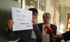 Neo aizstāves ar plakātu pieprasa atklātu lietas izskatīšanu