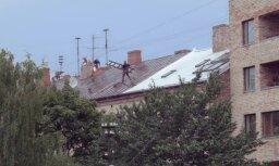 Video: Rīgā pārgalvīgi celtnieki rosās pa slapjo ēkas jumtu un apdraud apkārtējos