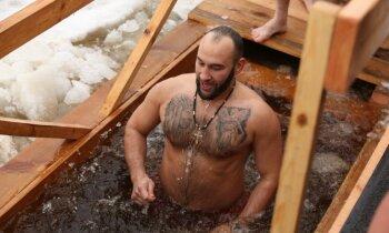 Foto: Ticīgie gremdējas iesvētītajos Daugavas ūdeņos