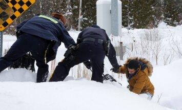Foto: Migranti no ASV brien pāri robežai uz Kanādu