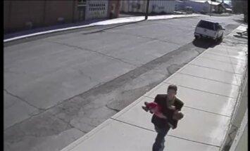ASV nofilmēts bērnu nolaupītājs, skrienot ar mazuli