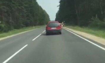 Video: Jaunietis mēģina izlēkt pa braucoša auto logu