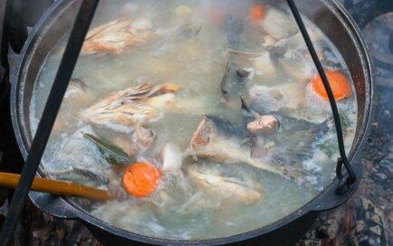 Virs ugunskura vārīta zivju zupa zaļumos