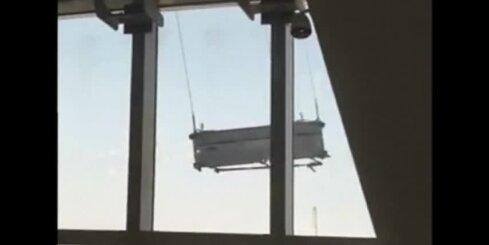Ķīnas debesskrāpja mazgātāji bīstami šūpojas pie 91. stāva logiem