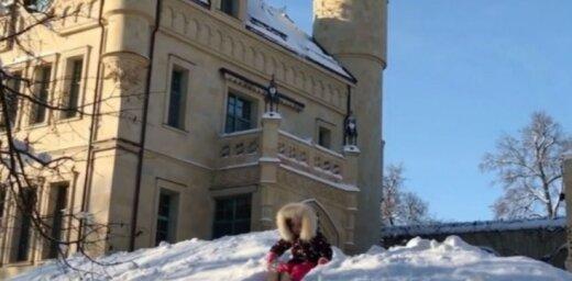 Galkins savas greznās pils pagalmā ar bērniņiem bauda ziemas priekus