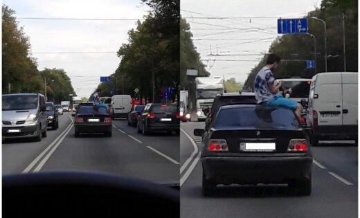 Foto: Pārgalvis traucas uz Juglu, sēžot uz auto jumta