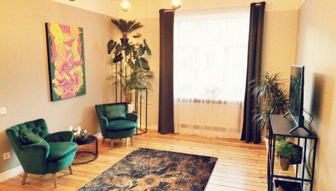 Ar telpaugiem, gleznām un klubkrēsliem dīvāna vietā: stilīgs dzīvoklis Rīgas centrā