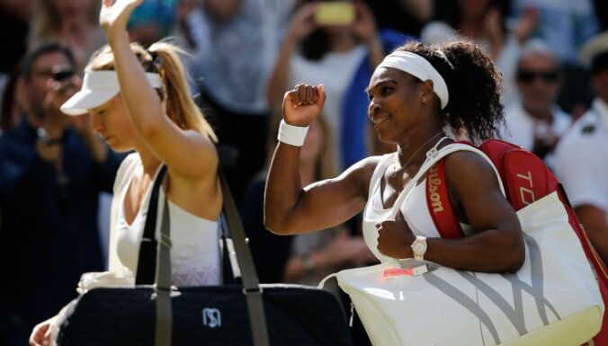Serena Williams (R) pumps her fist as she leaves the court with Russia s Maria Sharapova