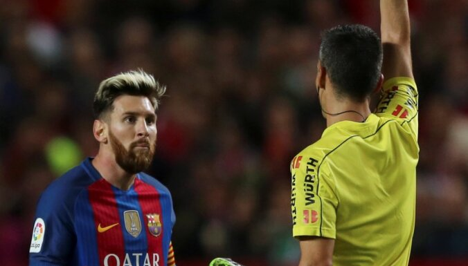 Barcelona s Lionel Messi receives a yellow card