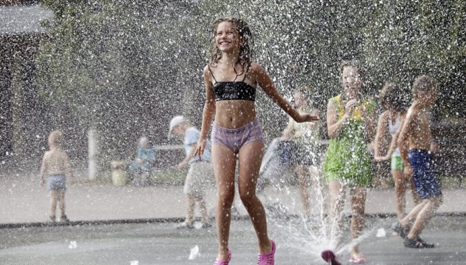 epa02251135 A girl enjoys the cooling effects of water jets   in a fountain in Podolsk 16 km. outside Moscow, Russia, 17 July  2010. A heat wave hit central Russia breaking temperature records going higher than 37 C.  EPA/YURI KOCHETKOV