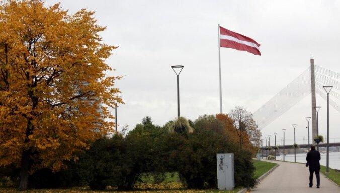 Foto: Uz AB dambja Rīgā atklāj milzu karogu