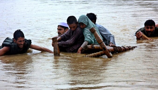 epa02265149 People flee their villages after heavy monsoon rains triggered flash floods in Charsadda a town of Khyber-Pakhtunkhwa province Pakistan on 29 July 2010. More than 100 people across the country have been killed and thousands stranded in the ong