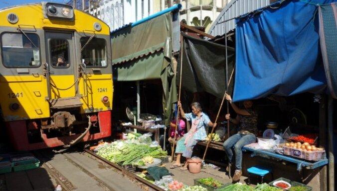Galvenais, ka andele – vilciens Taizemē, kas brauc cauri tipiskam Āzijas tirgum