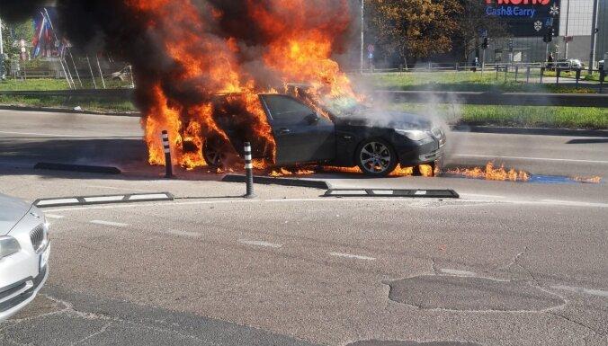 ФОТО. В Пурвциемсе на проезжей части загорелся BMW, на дороге образовался затор