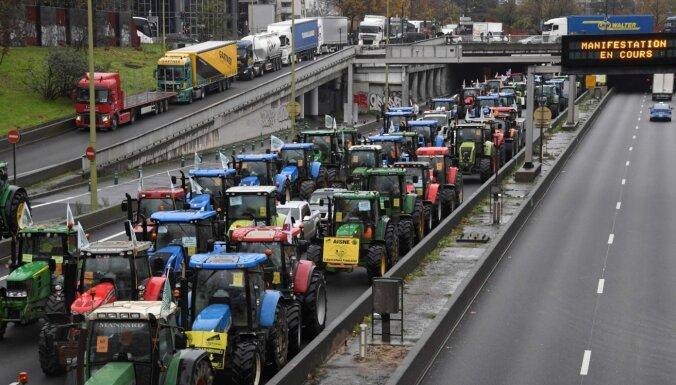 Foto: Lauksaimnieki Parīzē ar traktoriem nobloķē satiksmi