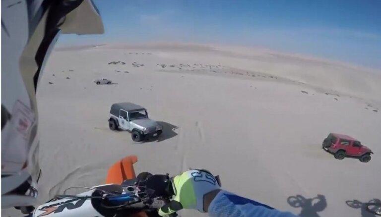 Video: Motokrosists lēcienā pār tuksneša kāpu negaidīti piezemējas uz džipa