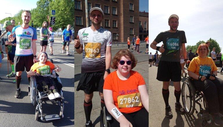 Iedvesmojošs jaunietis, stumjot cilvēkus ratiņkrēslā, Rīgas maratonā noskrien trīs distances