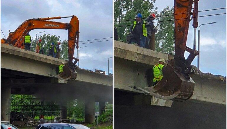 Foto: Salu tilta remontstrādnieks darbus veic ekskavatora kausā