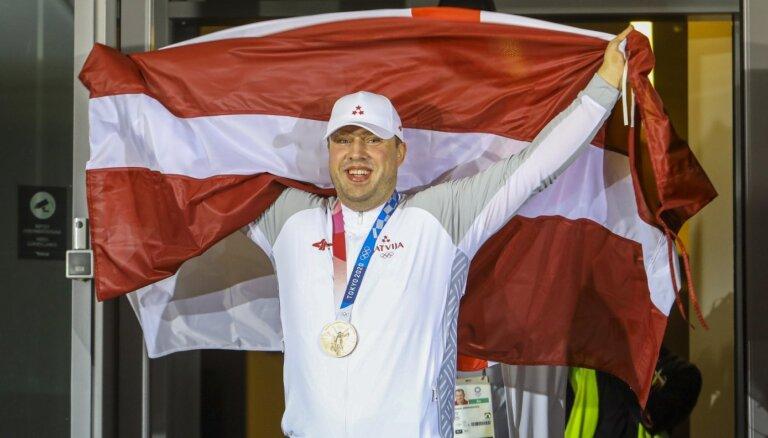 Latvijā sagaidīts Tokijas olimpisko spēļu bronzas medaļu izcīnījušais svarcēlājs Plēsnieks