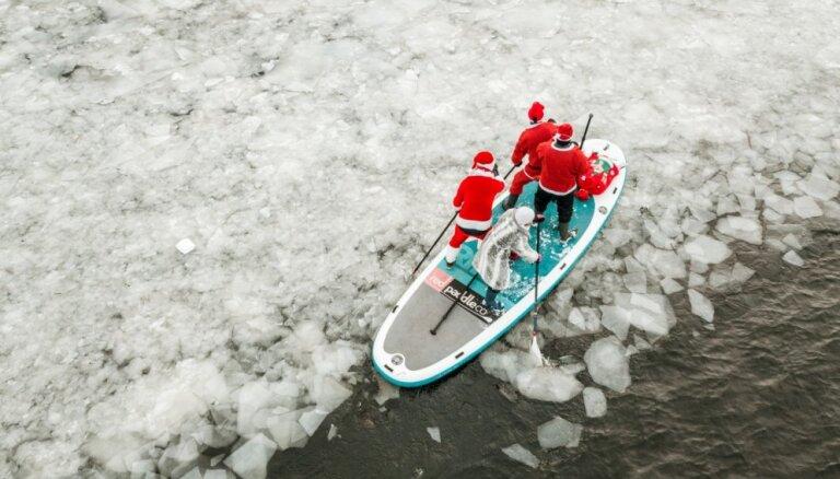 Foto: 'Ziemassvētku vecīši' ar SUP dēļiem iras pa ledaino Daugavu