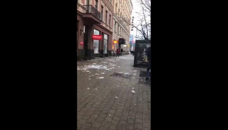 Video: Gājēji Rīgas centrā knapi izvairās no ledus, kas gāžas no jumta