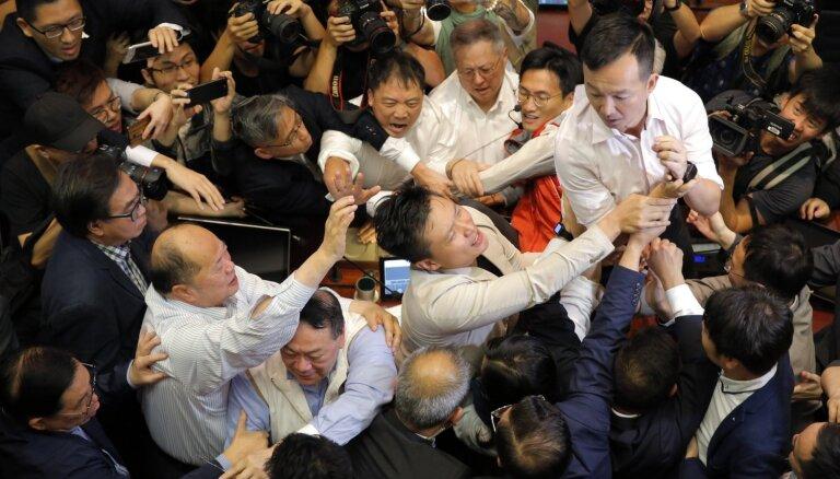 Kautiņā Honkongas parlamentā ievainoti četri deputāti