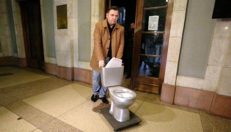Koncertzāles 'Rīga' kašķis: Millers LZA prezidentam Spārītim uzdāvina tualetes podu