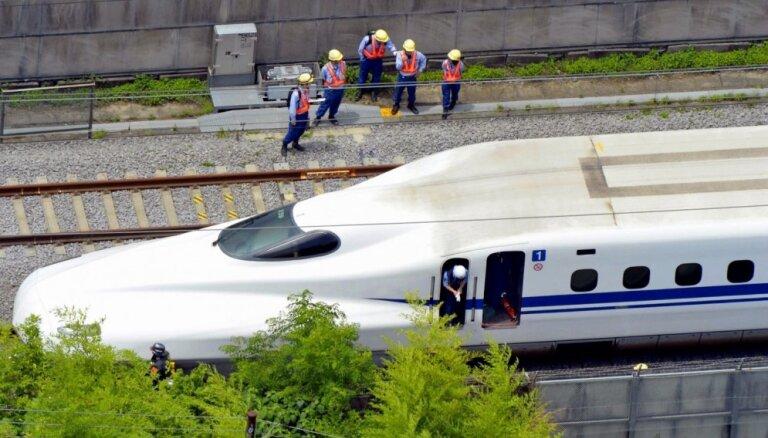 Japānas dzelzceļa darbinieki sēžas starp braucošiem vilcieniem treniņnolūkos